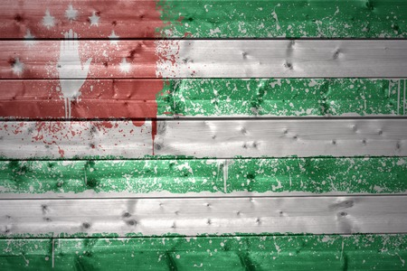 sukhumi: colorful painted abkhazian flag on a wooden texture