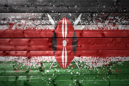 colorful painted kenyan flag on a wooden texture photo