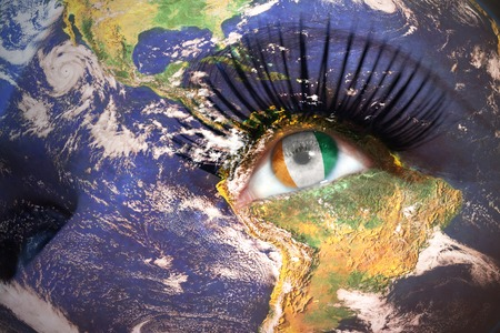 cote ivoire: womans face with planet Earth texture and cote Ivoire flag inside the eye Stock Photo