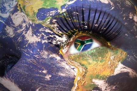 south africa flag: womans face with planet Earth texture and south africa flag inside the eye