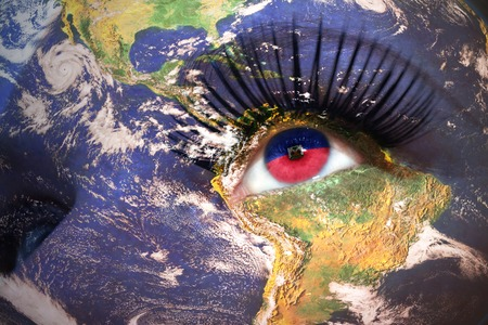 port au prince: woman face with planet Earth texture and haitian flag inside the eye