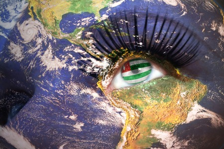 sukhumi: woman face with planet Earth texture and abkhazian flag inside the eye