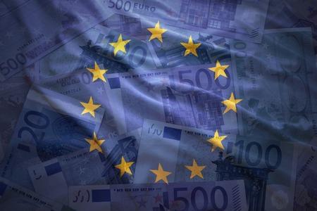 economia: colorido ondeando la bandera de la Unión Europea sobre un fondo de dinero del euro Foto de archivo