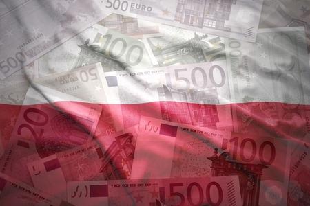 bandera de polonia: colorido agitando bandera polaca en un fondo de dinero del euro Foto de archivo