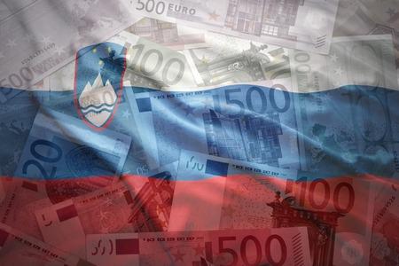 slovenian: colorful waving slovenian flag on a euro money background
