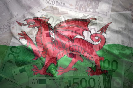 welsh flag: colorful waving welsh flag on a euro money background