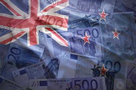 bandera de nueva zelanda: colorida bandera de Nueva Zelanda que agita en un fondo de dinero del euro Foto de archivo
