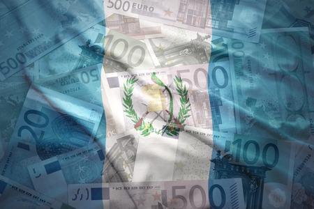 guatemalan: colorful waving guatemalan flag on a euro money background