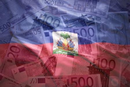 port au prince: colorido agitando bandera haitiana en un fondo de dinero del euro Foto de archivo