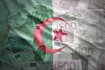algerian flag: colorful waving algerian flag on a euro money background Stock Photo