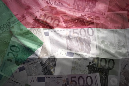 financial stability: colorful waving sudanese flag on a euro money background