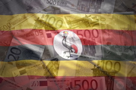 ugandan: colorful waving ugandan flag on a euro money background