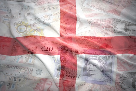 pound sterling: colorful waving english flag on a english pound sterling money background