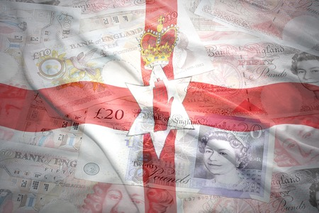 gb pound: colorful waving northern ireland flag on a english pound sterling money background