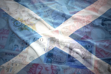 colorful waving scottish flag on a english pound sterling money background