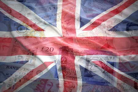 colorful waving british flag on a english pound sterling money background