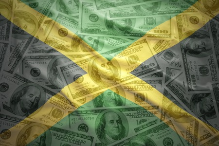 jamaican: colorful waving jamaican flag on a american dollar money background