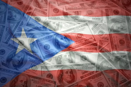 colorful waving puerto rican flag on a american dollar money background