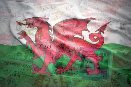 pound sterling: colorido agitando bandera galés en una libra Inglés dinero esterlina fondo