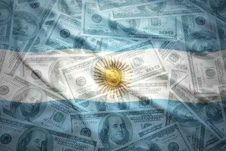 argentinean: colorful waving argentinean flag on a american dollar money background