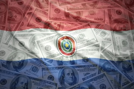 financial stability: colorful waving paraguayan flag on a american dollar money background Stock Photo