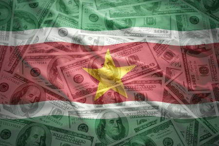 financial stability: colorful waving surinamese flag on a american dollar money background