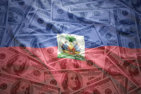port au prince: colorful waving haitian flag on a american dollar money background Stock Photo