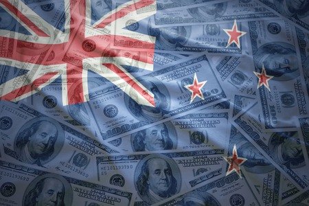 bandera de nueva zelanda: colorida bandera de Nueva Zelanda que agita en un fondo de dinero americano de dólar