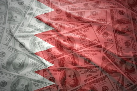 bahrain money: colorful waving bahrain flag on a american dollar money background Stock Photo