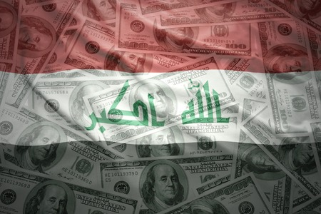iraq money: colorful waving iraqi flag on a american dollar money background