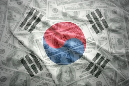 colorful waving south korea flag on a american dollar money background