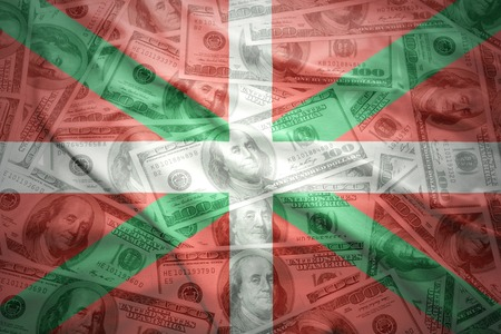 the basque country: colorful waving basque country flag on a american dollar money background