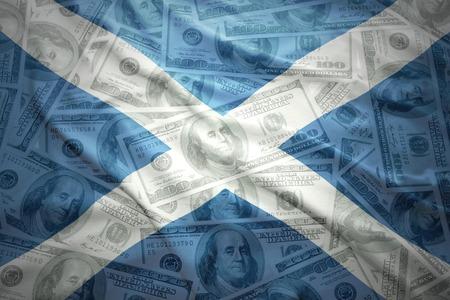 scottish flag: colorato sventola bandiera scozzese su uno sfondo di denaro dollaro americano Archivio Fotografico