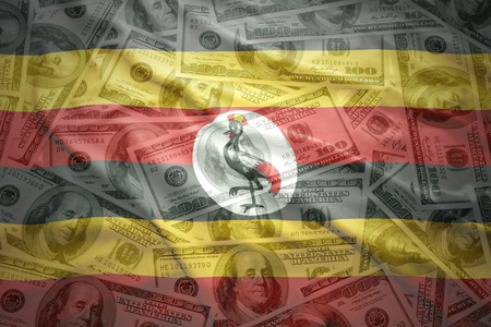 ugandan: colorful waving ugandan flag on a american dollar money background