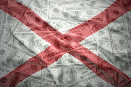 alabama state: colorful waving alabama state flag on a american dollar money background