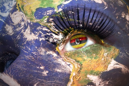 kampala: womans face with planet Earth texture and ugandan flag inside the eye.  Stock Photo