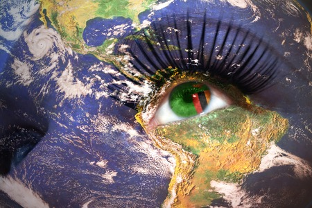 zambian flag: womans face with planet Earth texture and zambian flag inside the eye.