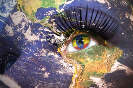 ethiopian: womans face with planet Earth texture and ethiopian flag inside the eye.
