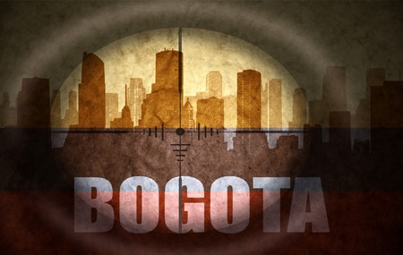 colombian flag: sniper scope aimed at the abstract silhouette of the city with text Bogota at the vintage colombian flag. concept