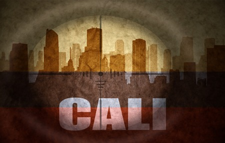 colombian flag: sniper scope aimed at the abstract silhouette of the city with text Cali at the vintage colombian flag. concept