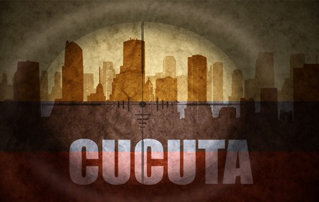the name of the drug: sniper scope aimed at the abstract silhouette of the city with text Cucuta at the vintage colombian flag. concept Stock Photo