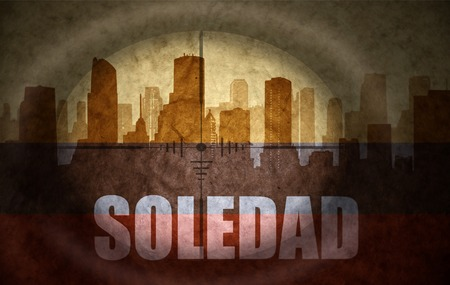 colombian flag: sniper scope aimed at the abstract silhouette of the city with text Soledad at the vintage colombian flag. concept