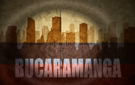 the name of the drug: sniper scope aimed at the abstract silhouette of the city with text Bucaramanga at the vintage colombian flag. concept Stock Photo