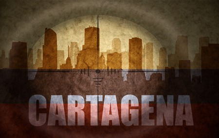 the name of the drug: sniper scope aimed at the abstract silhouette of the city with text Cartagena at the vintage colombian flag. concept Stock Photo