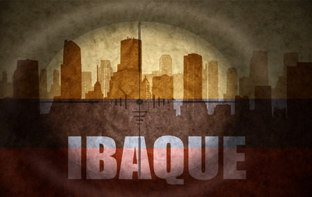the name of the drug: sniper scope aimed at the abstract silhouette of the city with text Ibague at the vintage colombian flag. concept