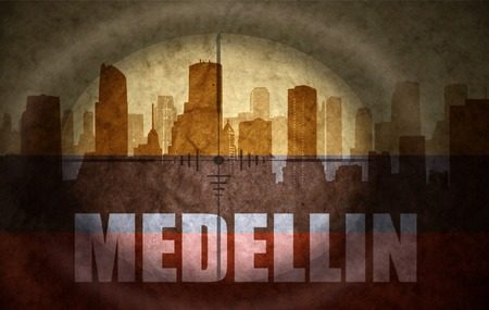 colombian flag: sniper scope aimed at the abstract silhouette of the city with text Medellin at the vintage colombian flag. concept
