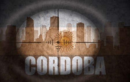the name of the drug: sniper scope aimed at the abstract silhouette of the city with text Cordoba at the vintage argentinian flag. concept
