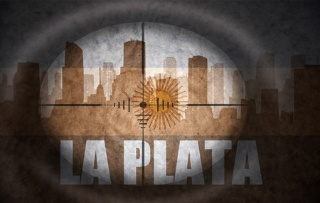 argentinian flag: sniper scope aimed at the abstract silhouette of the city with text La Plata at the vintage argentinian flag. concept