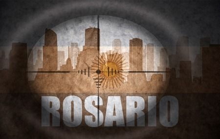 argentinian flag: sniper scope aimed at the abstract silhouette of the city with text Rosario at the vintage argentinian flag. concept
