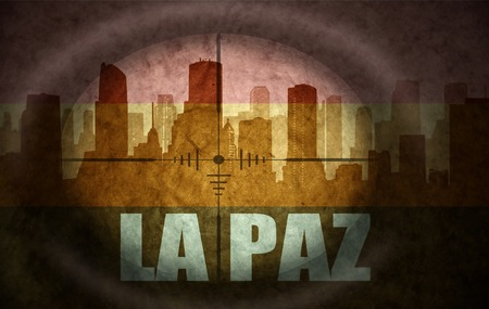 the name of the drug: sniper scope aimed at the abstract silhouette of the city with text La Paz at the vintage bolivian flag. concept Stock Photo